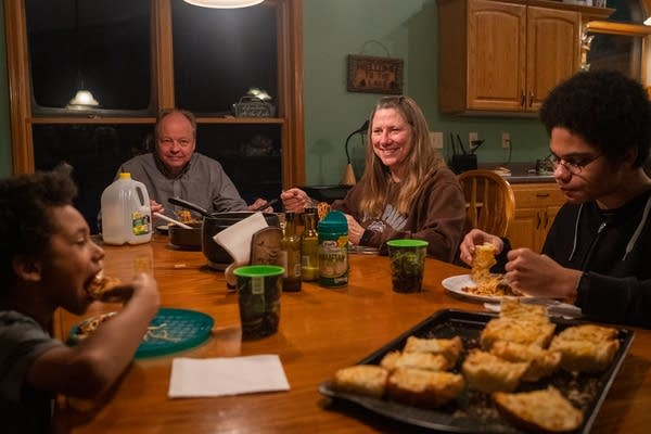 A family of 4 eats a spaghetti dinner at a table.