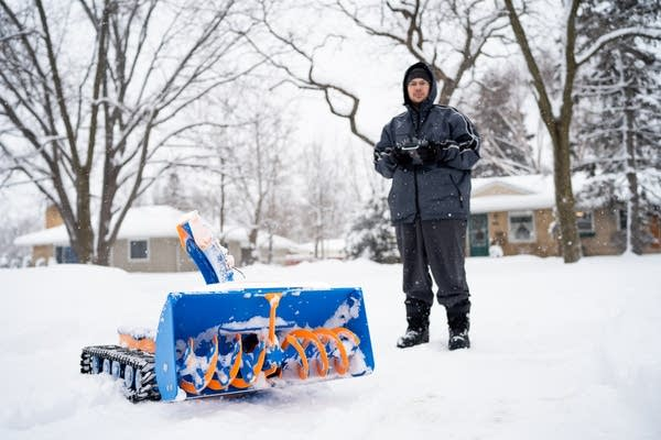 Ryan Butler stands with the snow blower robot he made.