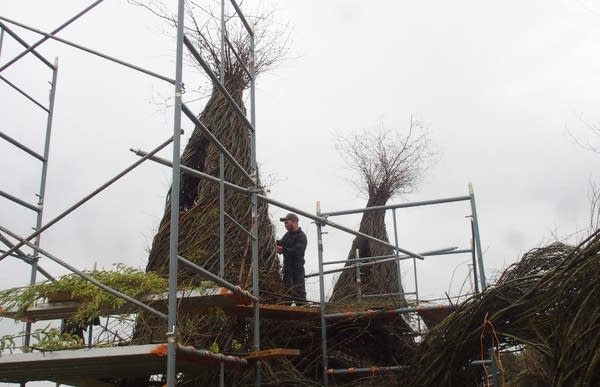 Patrick Dougherty's son Sam works on one of the spires.