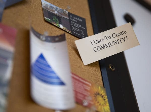 "A card on a bulletin board says ""I dare to create community."""