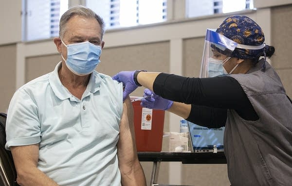 A man getting vaccinated by a nurse.