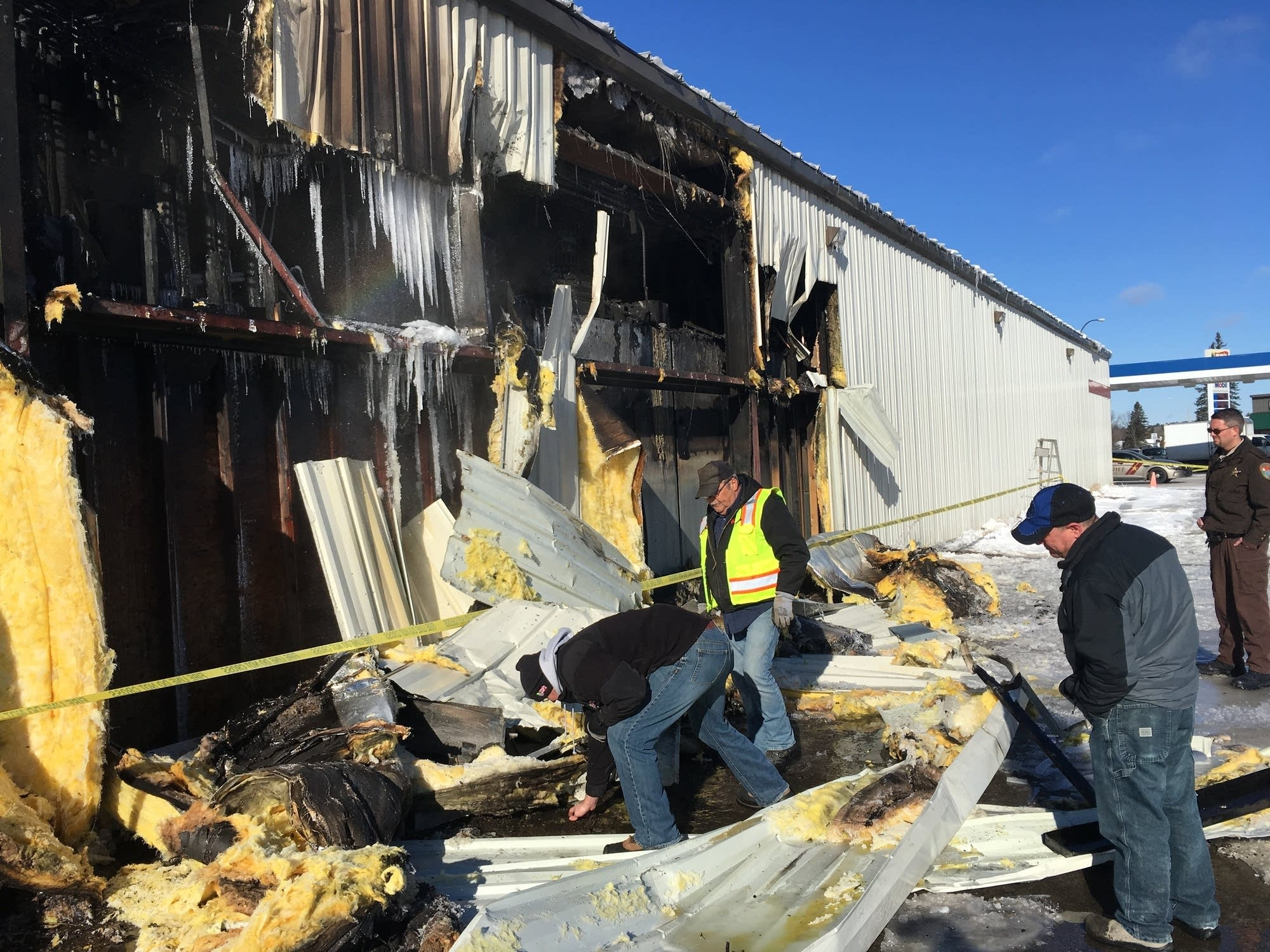 Zup's grocery store manager Matt Zupancich clears away metal siding.