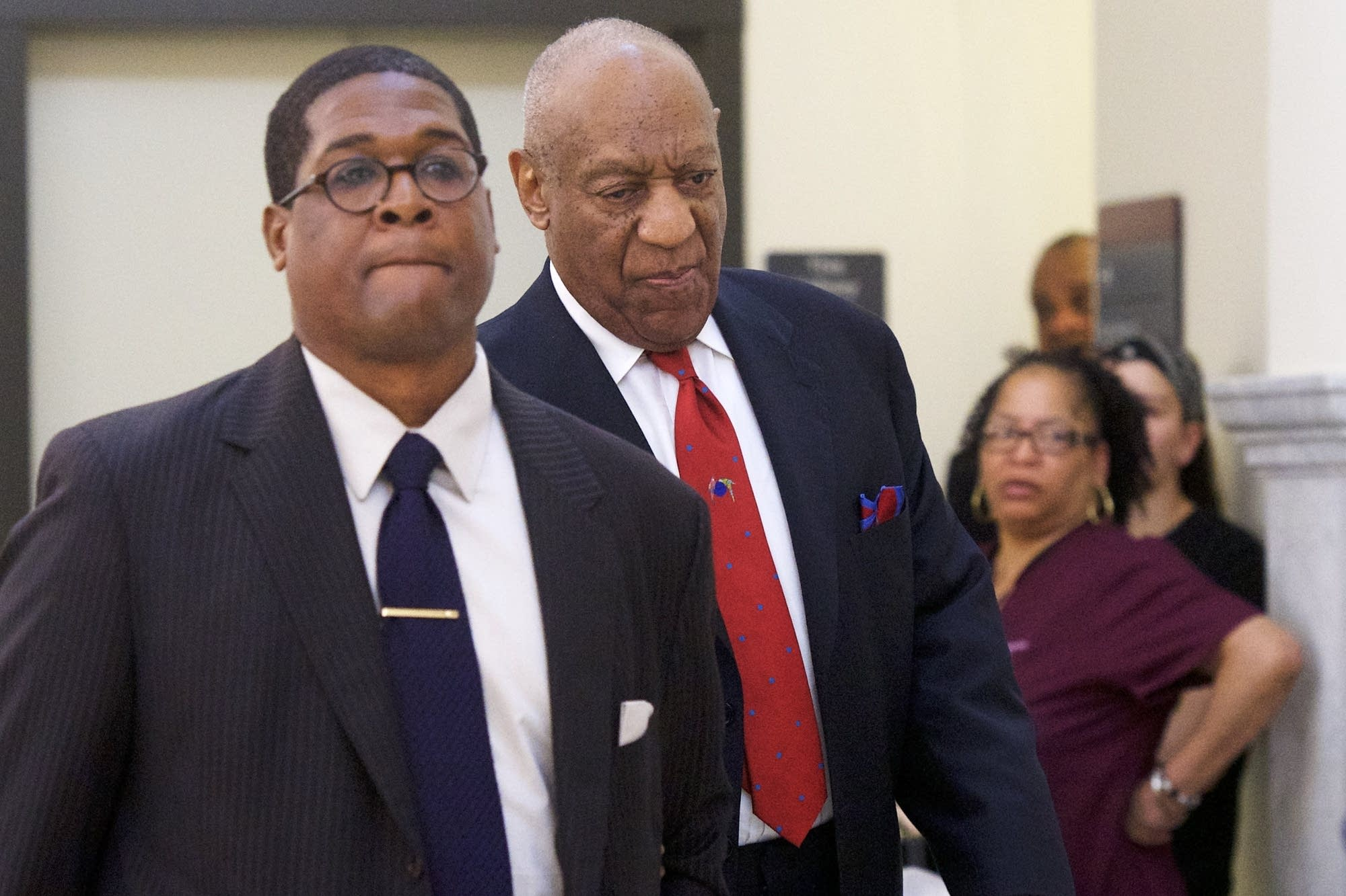 Bill Cosby (C) walks through the Montgomery County Courthouse
