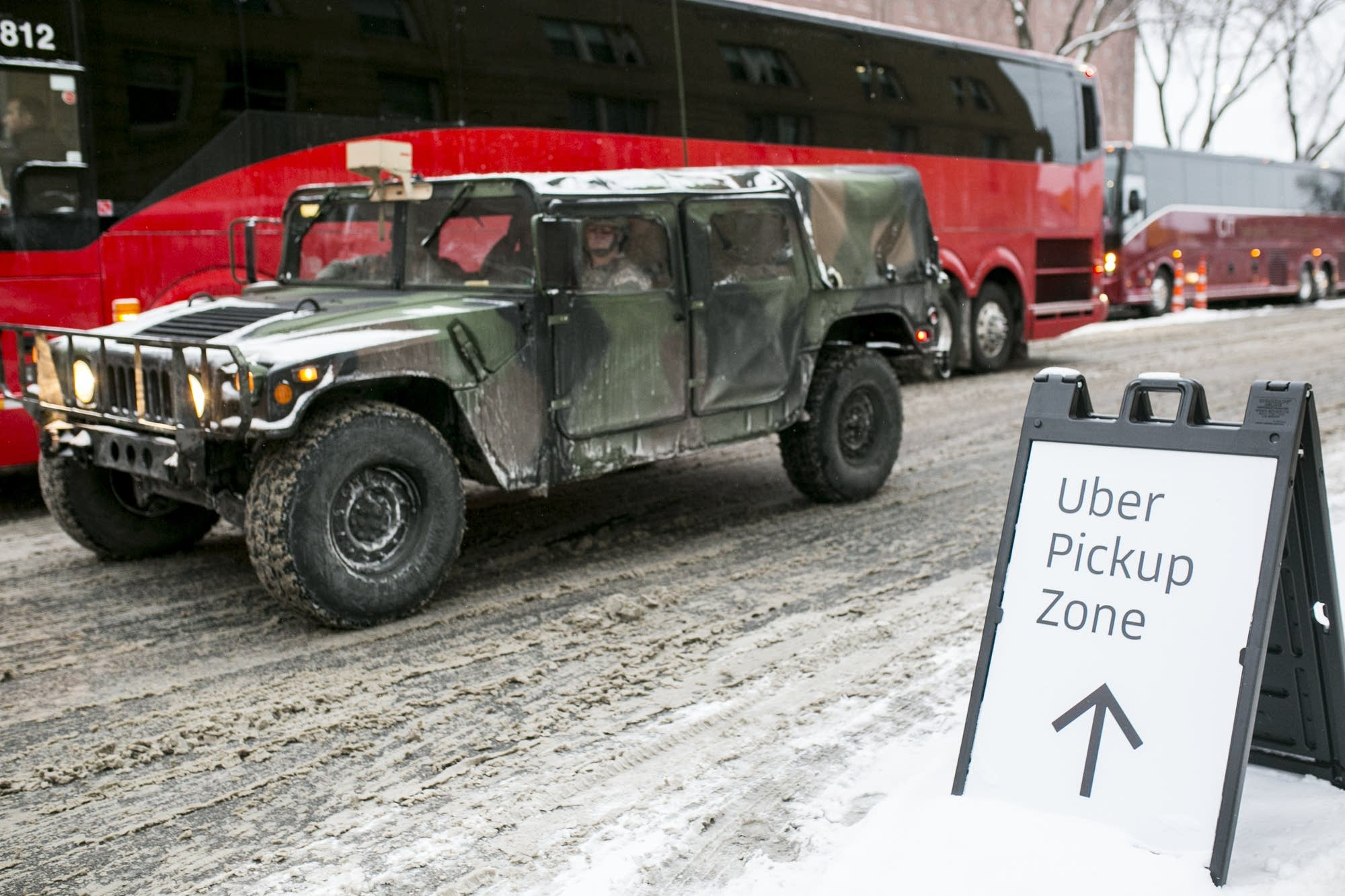 A military Humvee drives past a sign for an Uber pickup zone