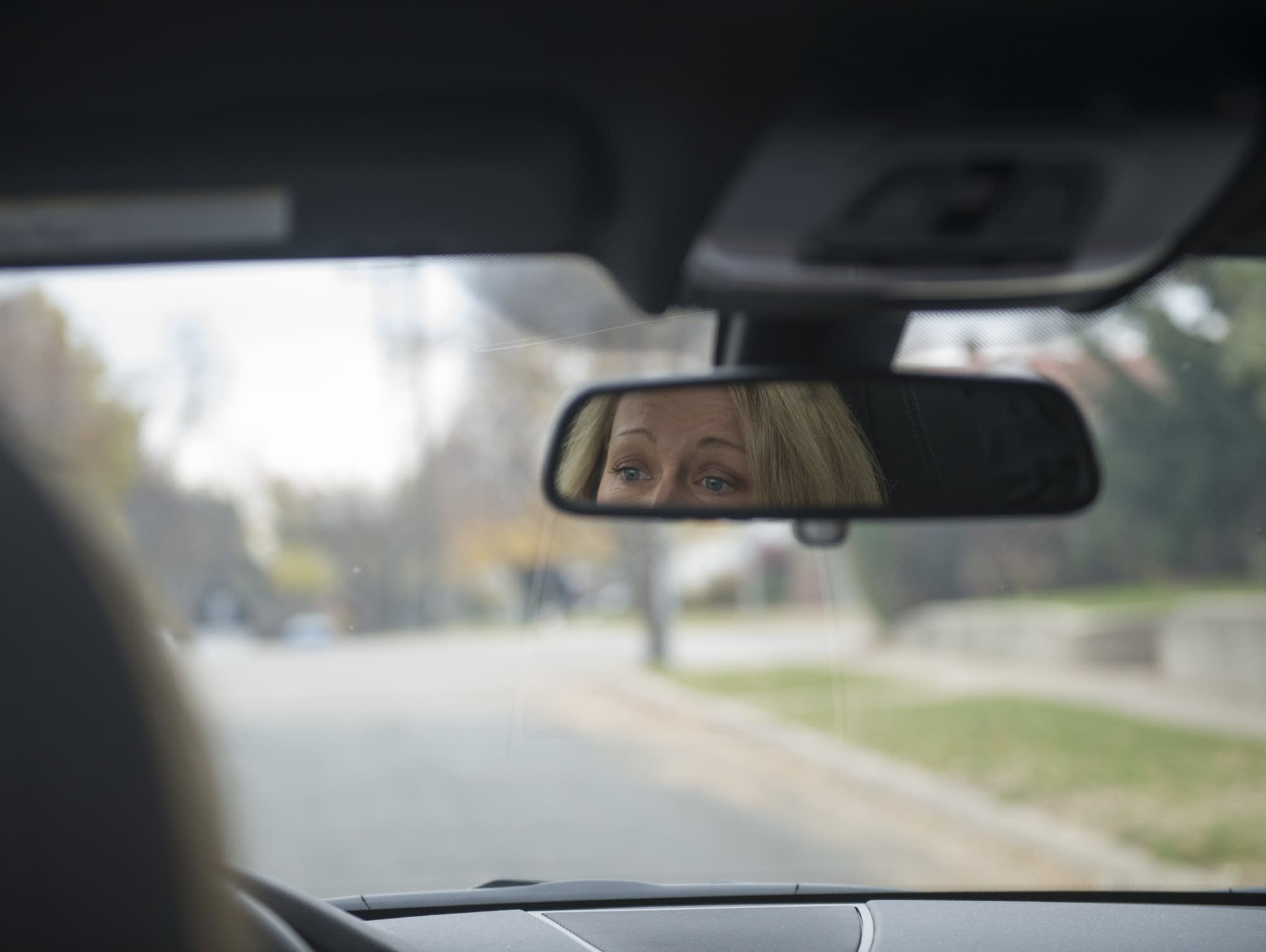 Heather Edelson's reflection is seen in the rearview while she drives.