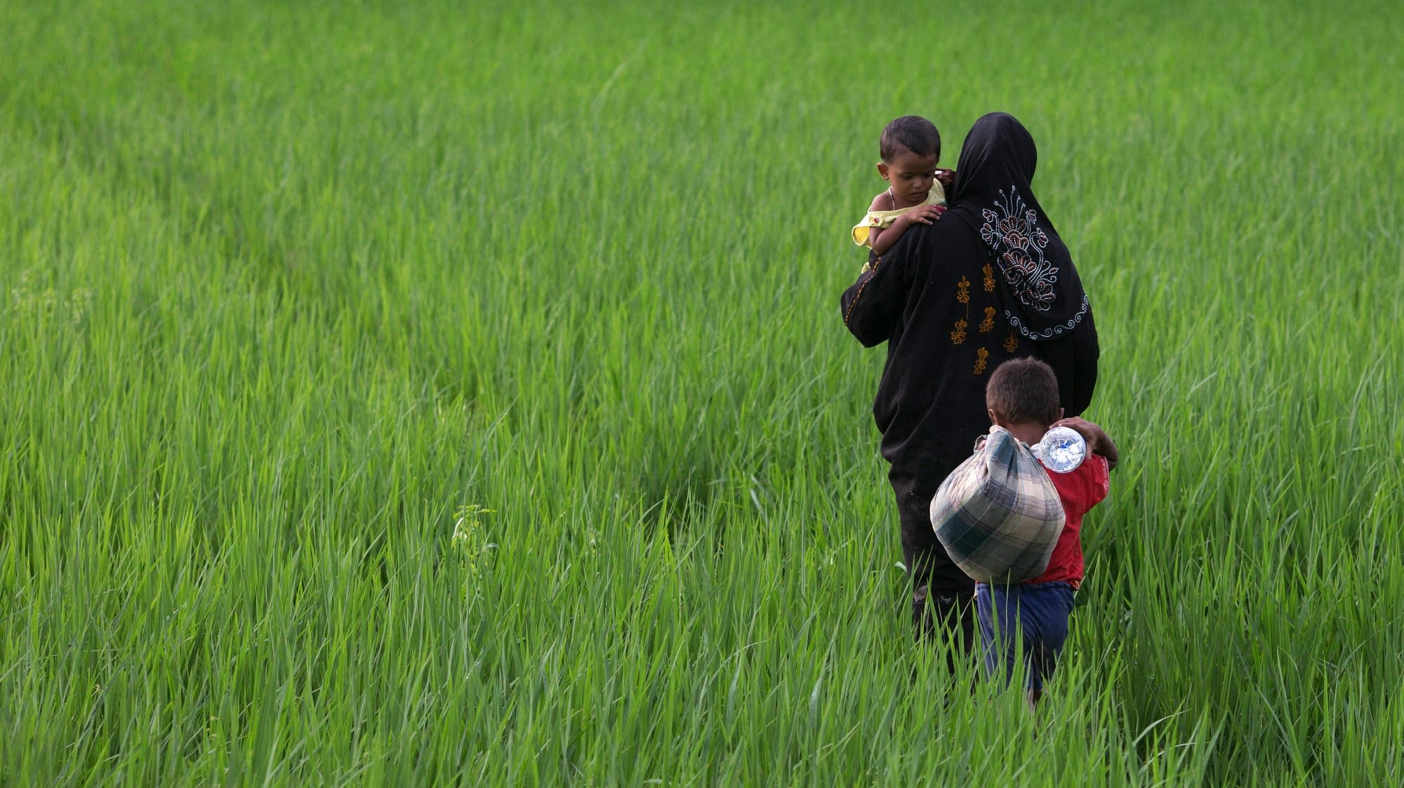 A Rohingya mother carries one child and leads another