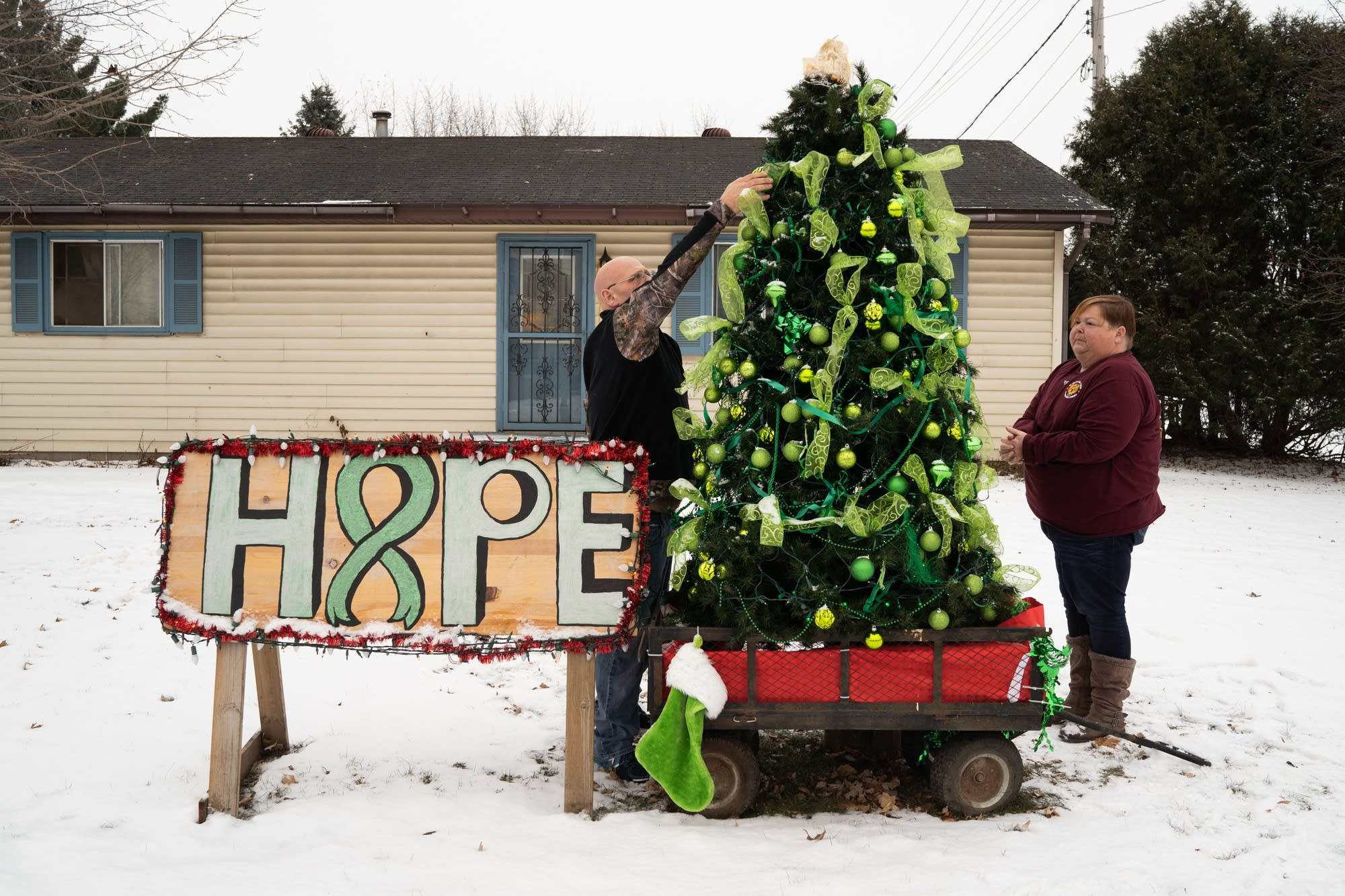 David White and Amy Stone put ornaments back on a tree in their front yard.