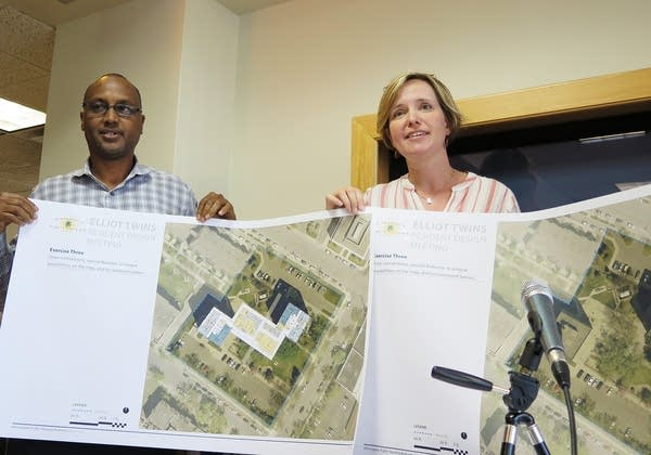A man and a woman hold a rendering of apartment buildings.