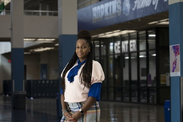 A Black woman stands in a school hallway.