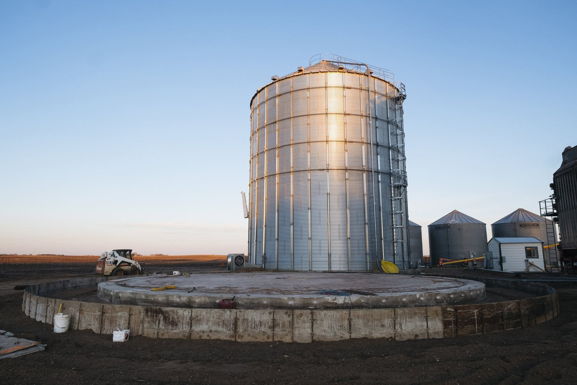 The sun sets on the grain storage site.
