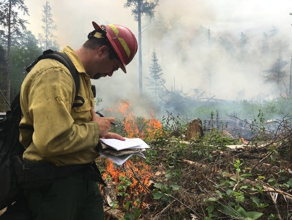 Jeb Bokke writes notes as a prescribed fire burns behind him