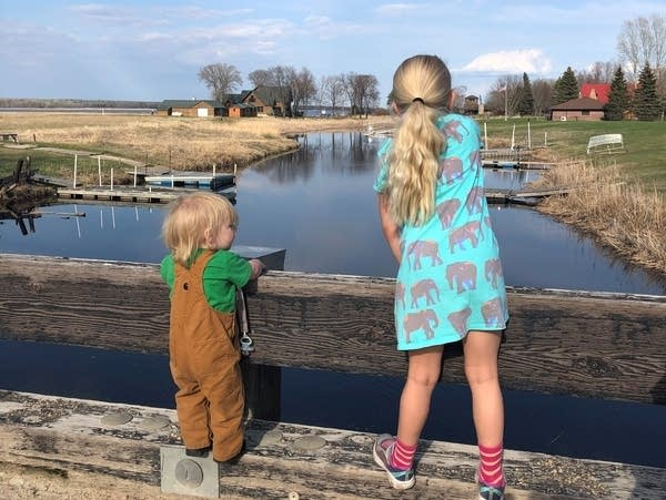 Two children look over a lake.