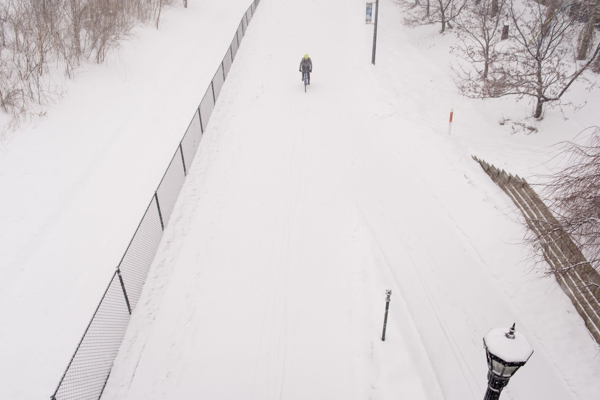 A cyclist braves snowy conditions riding on the Midtown Greenway.