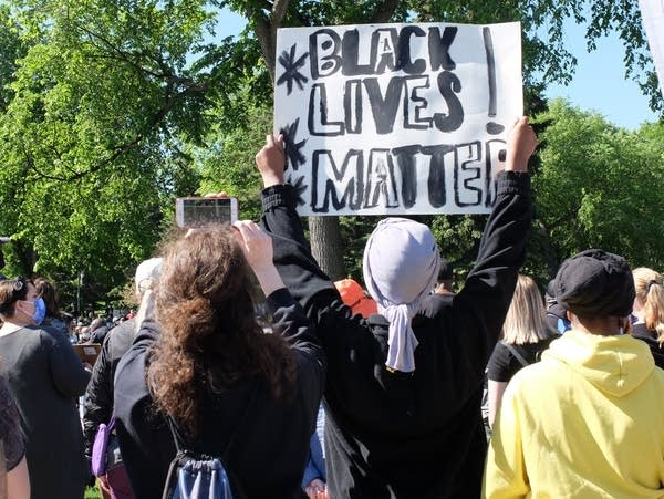 A person holds a sign saying Black Lives Matter