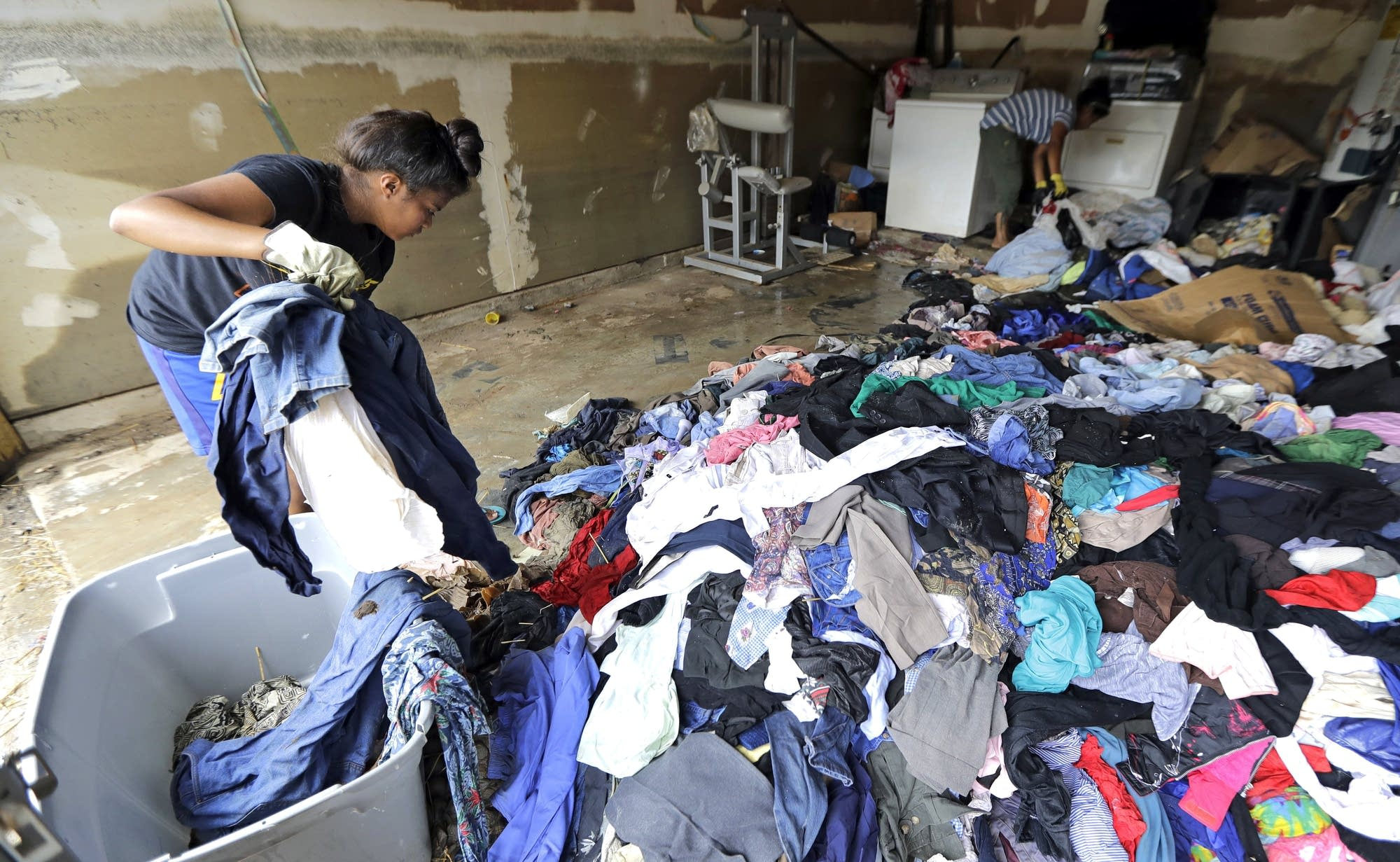 Women remove cloting from their Houston home, destroyed by floodwaters