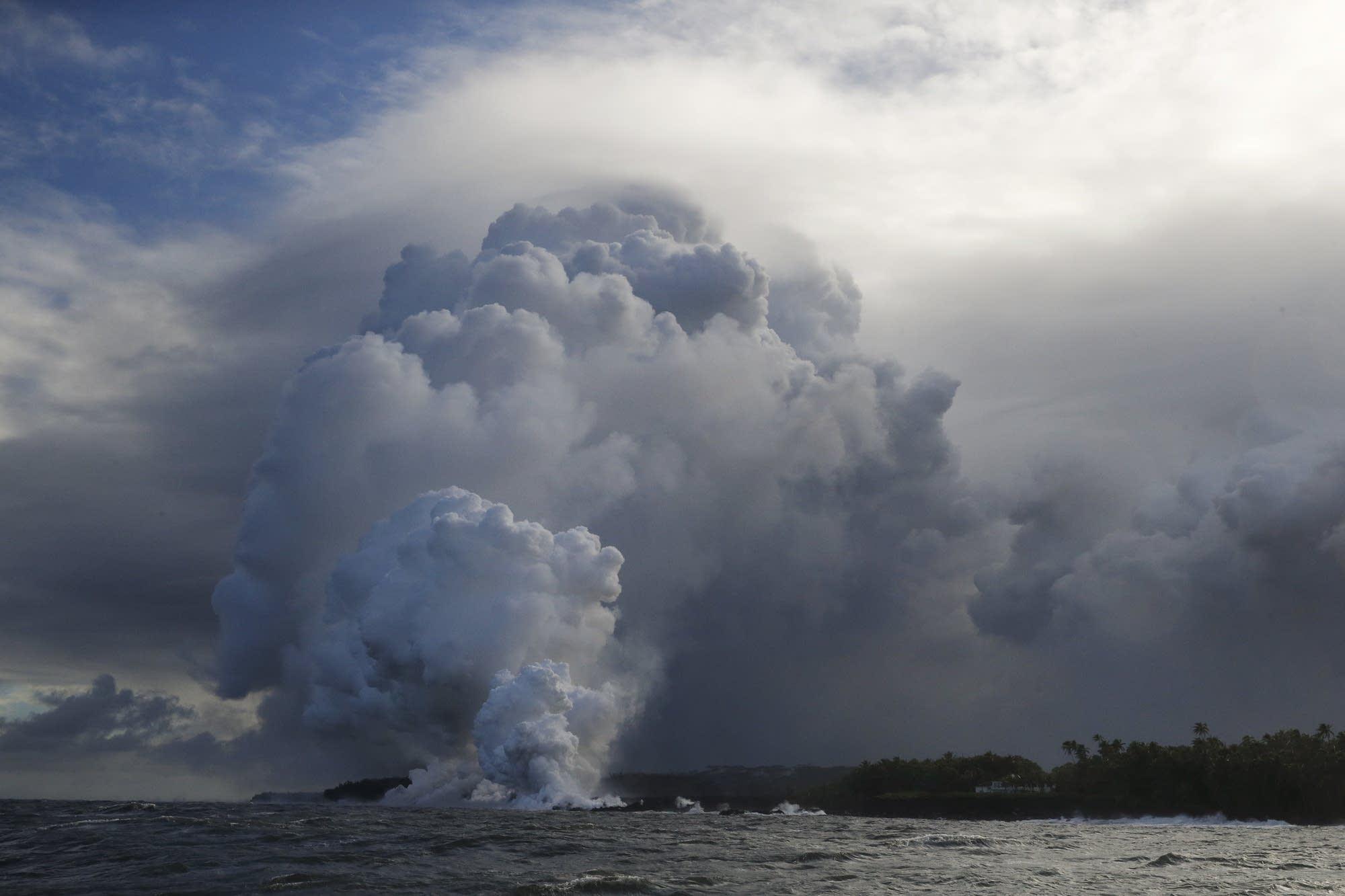 A plume of steam rises as lava enters the ocean near Pahoa, Hawaii.