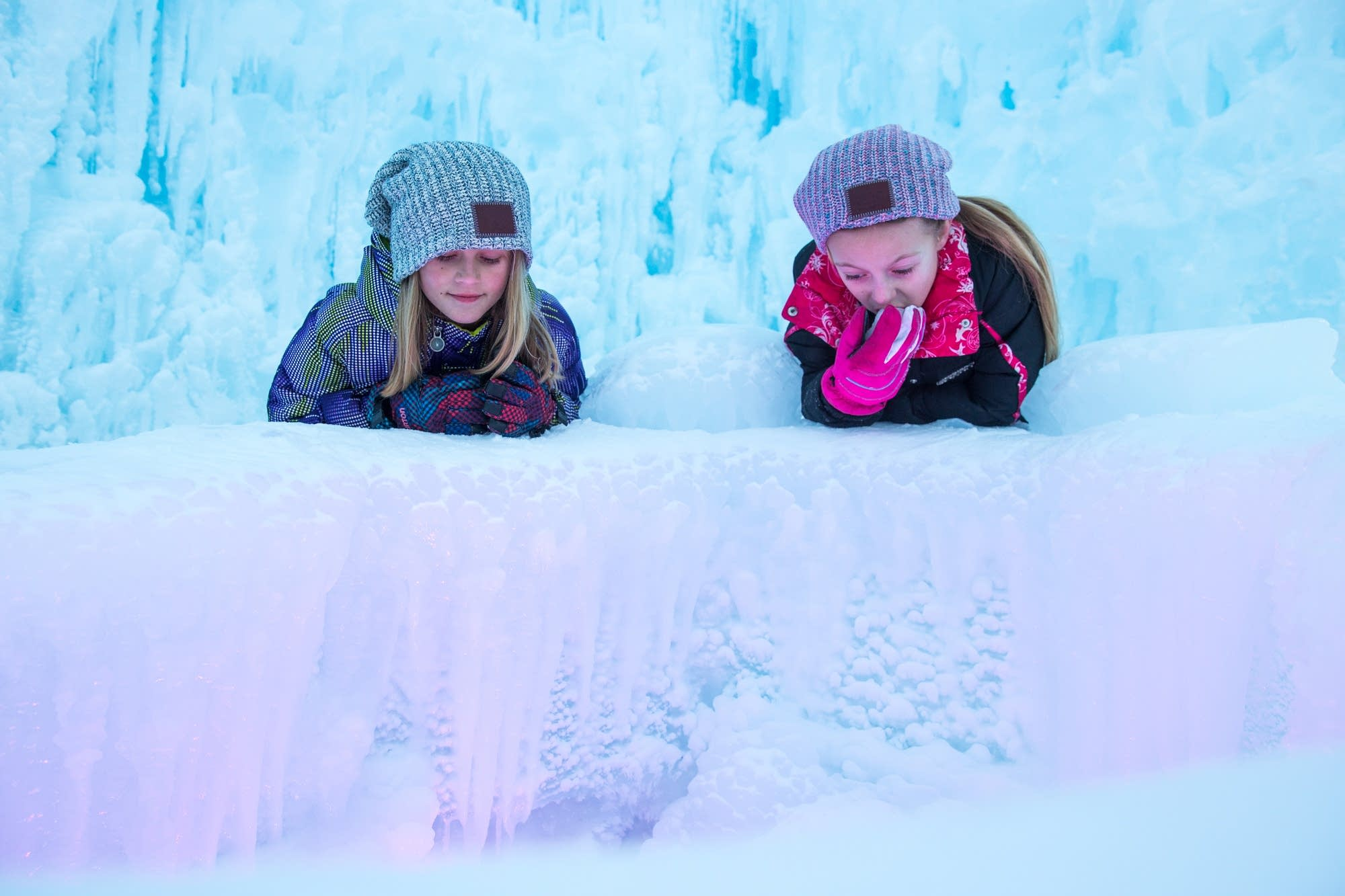 Young girls peer into an ice chasm,
