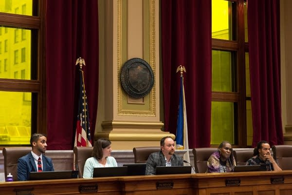 City council members listen at a hearing.