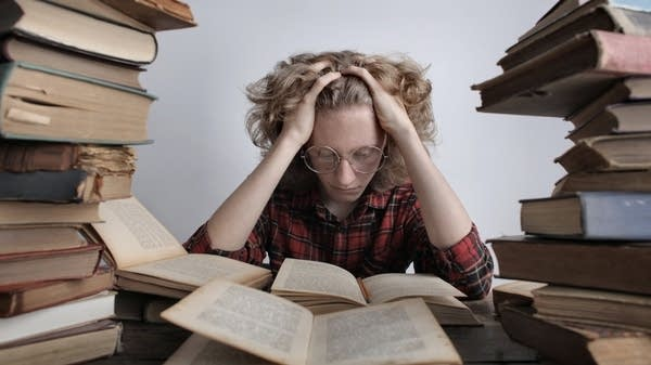 A photo illustration of a student stressed while reading.