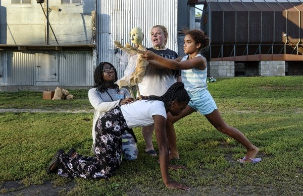 Local youth act out a scene with a puppet representing Minnesota Woman
