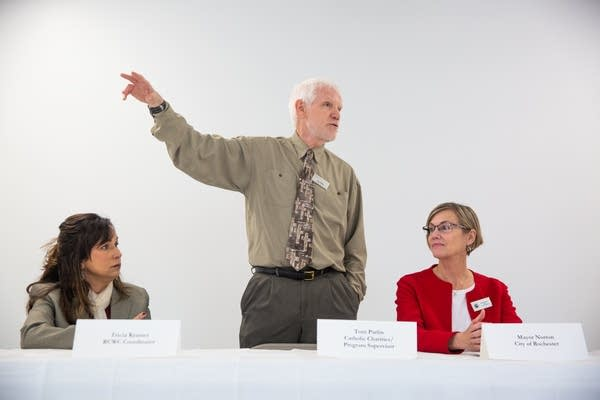 A man speaks in front of a white wall in between two women sitting.
