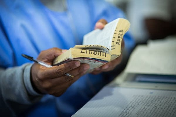An inmate flips through a well-used paperback