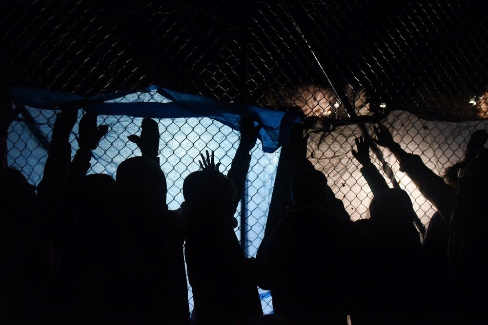 Protesters outside a police fence.