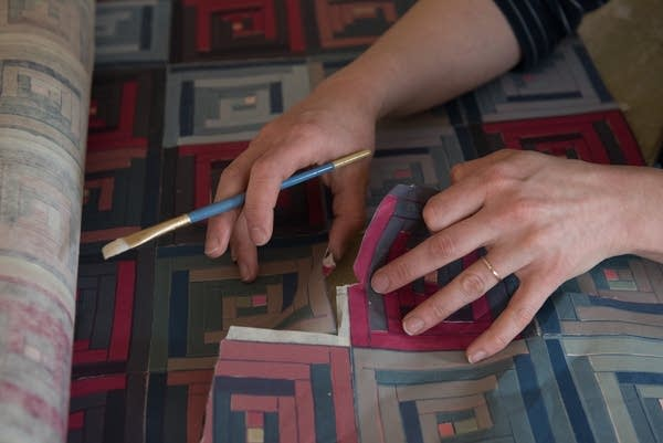 Artist Katy Collier works on a woodcut collage.