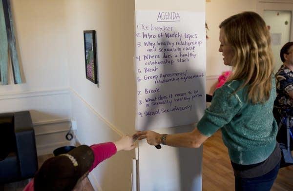 A participant helps Katy Park hang the agenda.