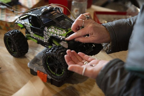 Close up of hands putting silver rhinestones on a green remote control car