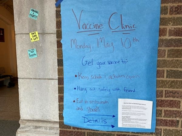 A sign on a wall provides details for a school vaccine clinic.