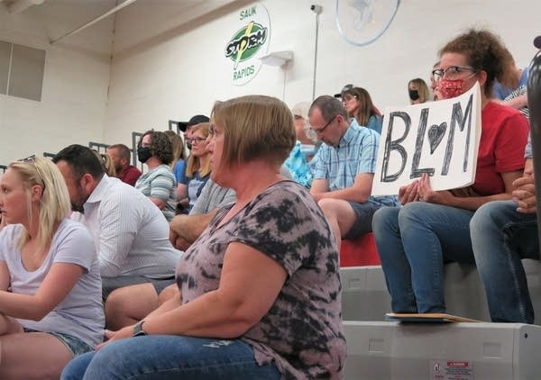 People hold signs on bleachers.
