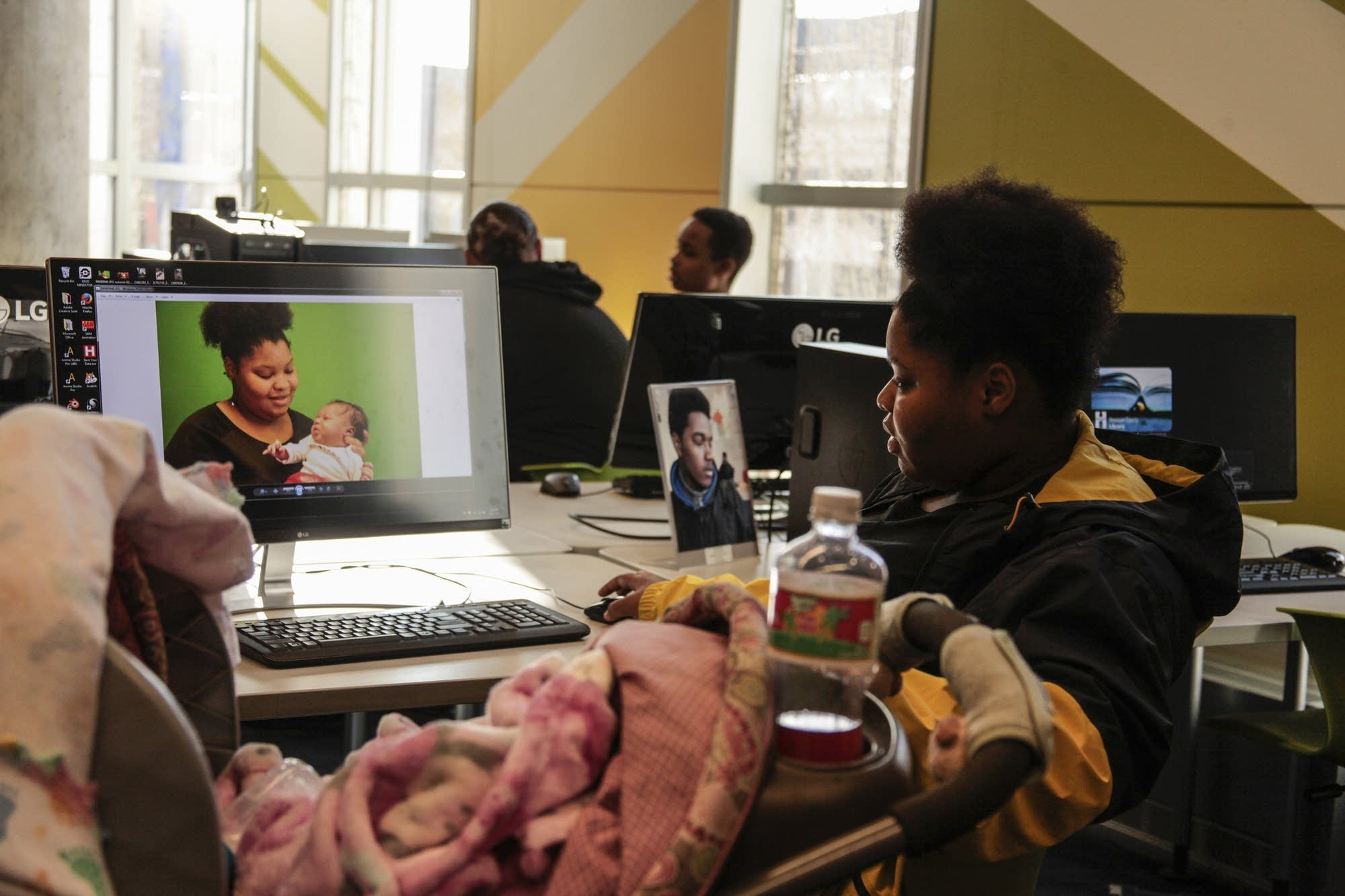 A teen mom edits a photograph of her and her newborn on the computer.
