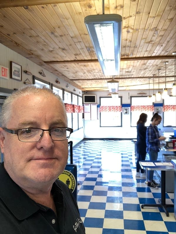 A man poses in a photo of a business that has two customers and no tables.