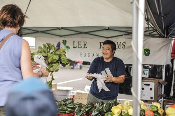 Mao Lee sells produce at the Maple Grove Farmers Market