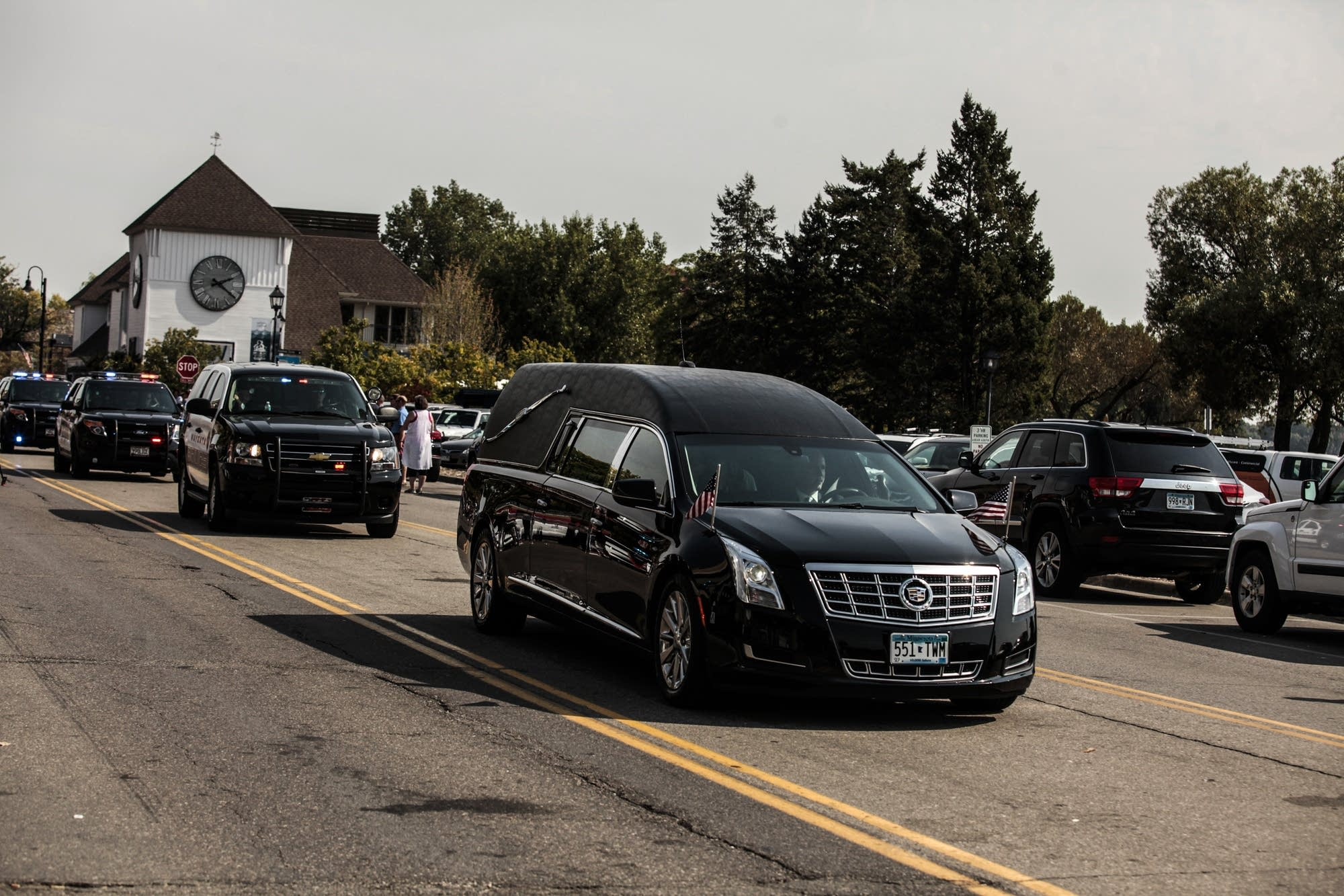 A hearse carries officer Mathews to the cemetery.