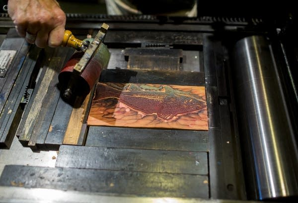 Bowen applies ink to a red fish wood block.