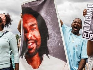 John Thompson, a friend of Philando Castile, holds his photo in a march.