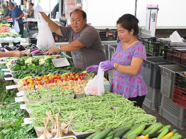 Two people sell vegetables at a farmer's market.