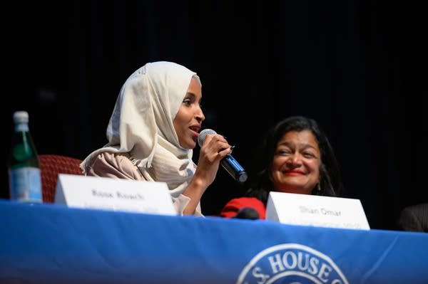 A woman holds a microphone as she speaks at a panel discussion.