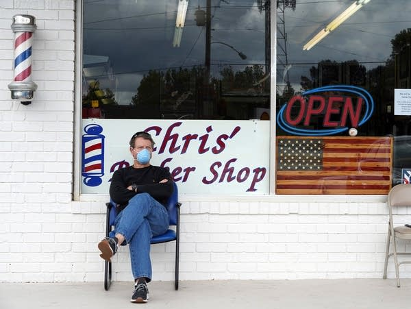 A man sits outside of an open barber shop business.