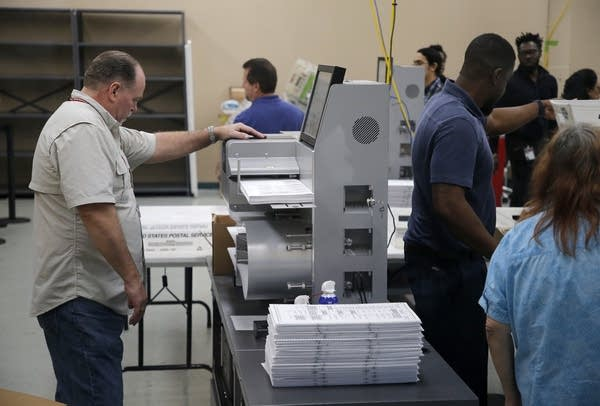 Elections staff load ballots into machine as recounting begins.