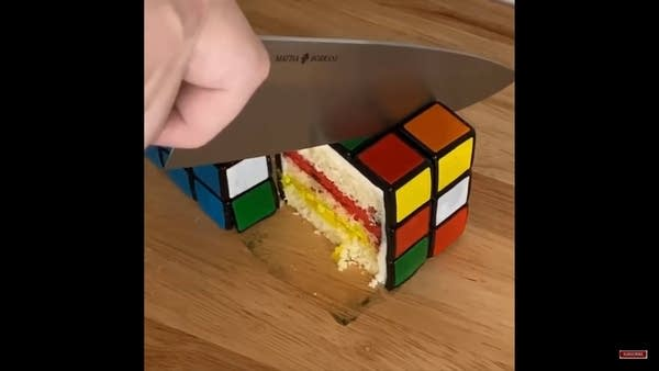 A hand with a knife cutting into a cake that looks like a real Rubik's Cube
