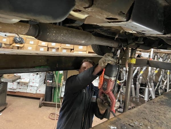 A man saws through the exhaust pipe under a Saturn SUV.