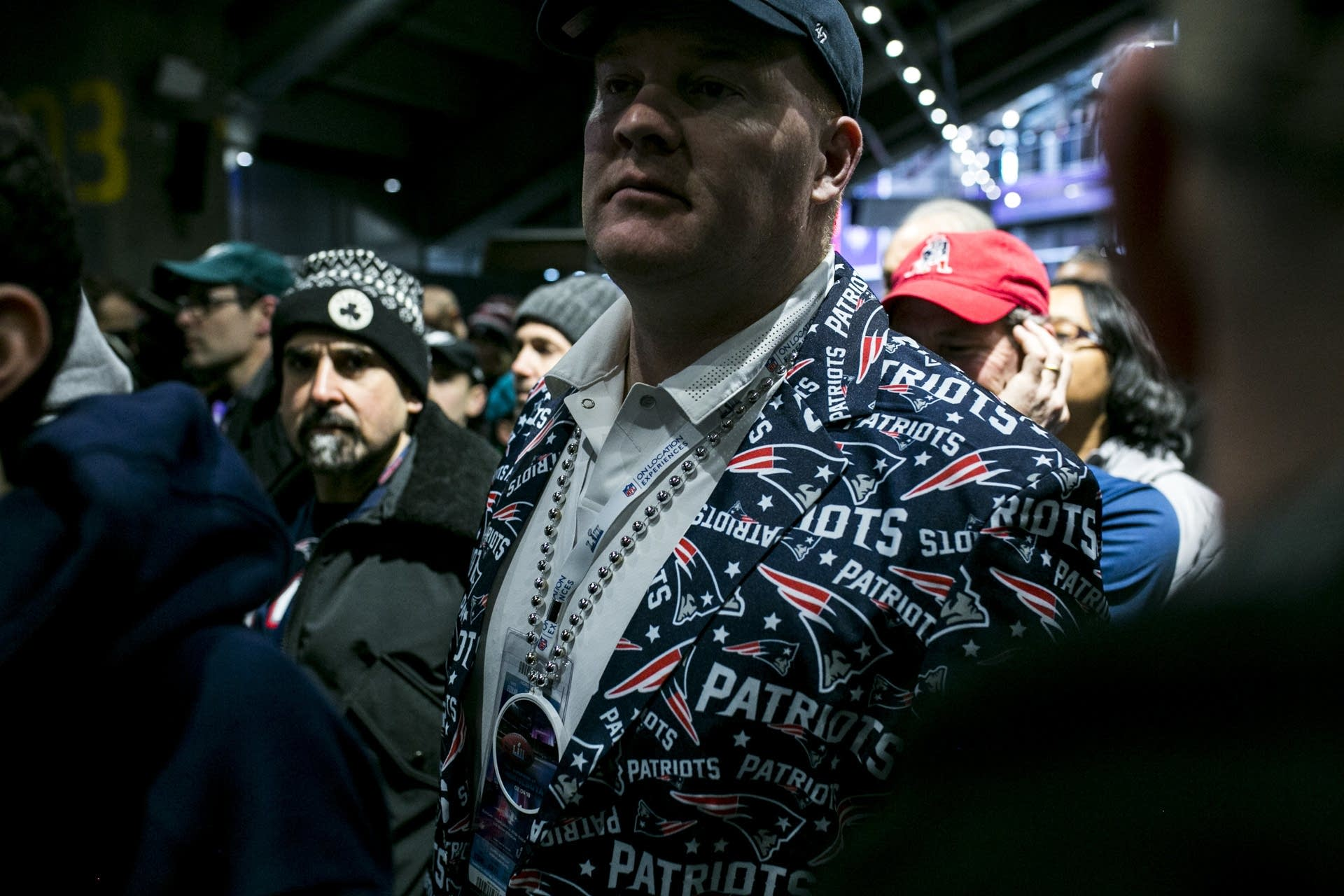 A man wearing a Patriots blazer cuts through the crowd.