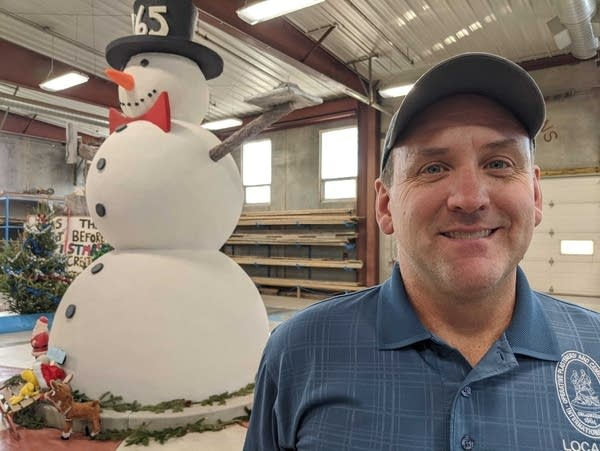A man is standing in front of a concrete snowman.