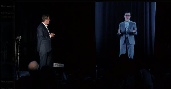 Man standing on stage with hologram of another man