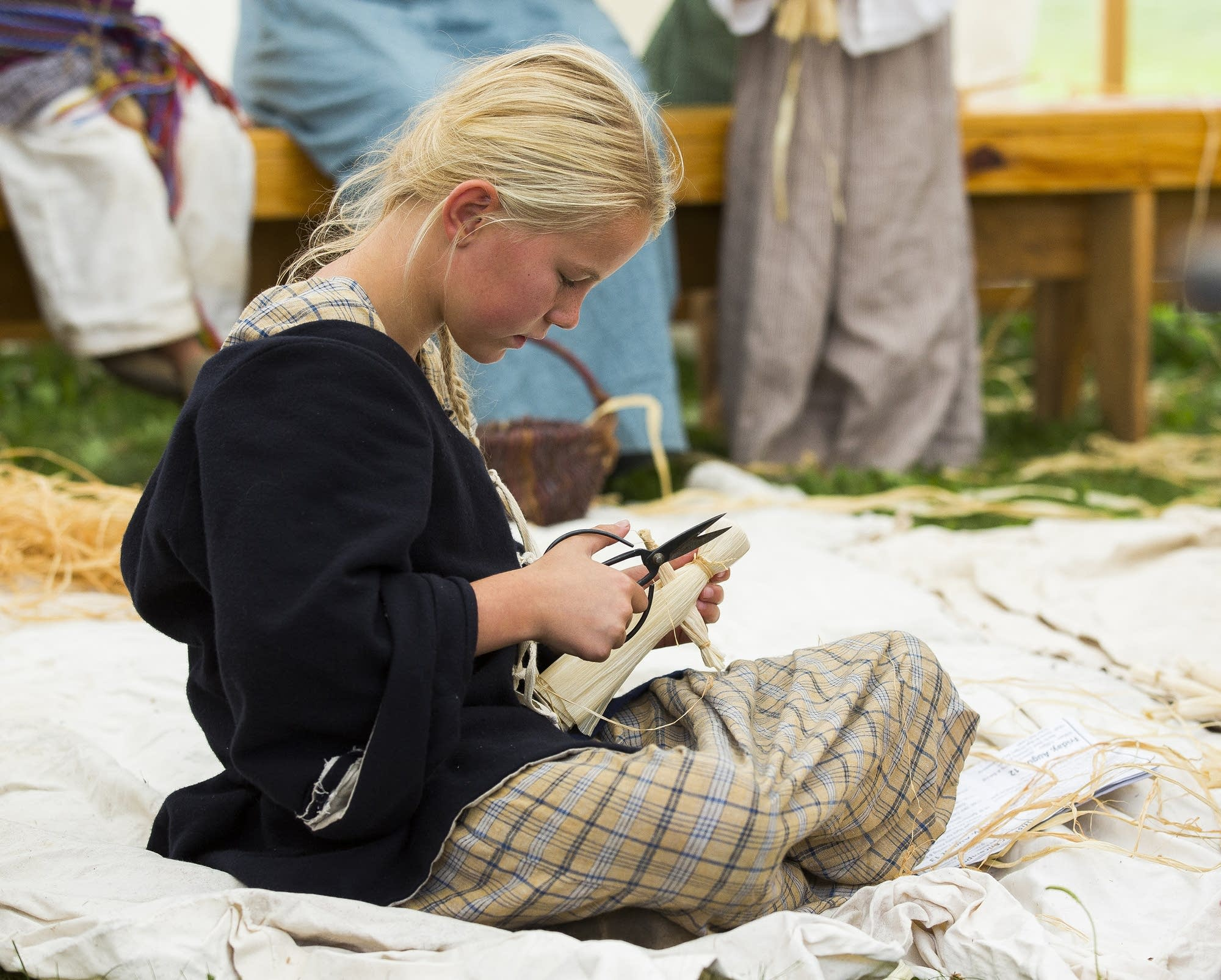 Ella Halverson works on a corn husk doll.