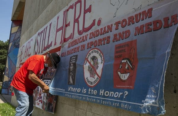A man puts up a banner outside a building.