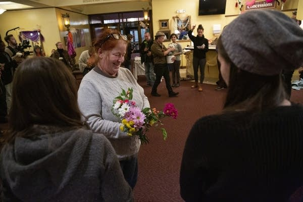 A woman hands out flowers to people standing in a circle.